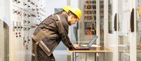 Twee onderhoudstechnici inspecteren het relaisbeveiligingssysteem met een laptopcomputer. Bay-regeleenheid. Middenspanningsschakelapparatuur