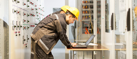 Two maintenance engineers inspect relay protection system with laptop computer. Bay control unit. Medium voltage switchgear Standard-Bild - 94401874