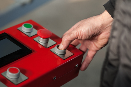 Industrial machinery mechanics and factory worker adjusts industry machine and checks if everything works properly Stock Photo