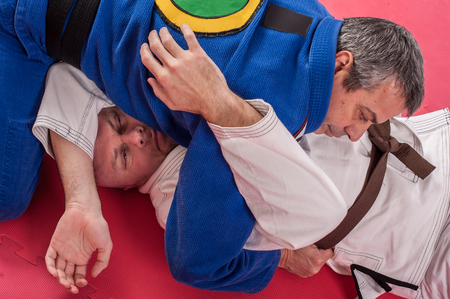 Kapap and brazilian jiu jitsu instructor in traditional kimono demonstrates ground fighting arm lock techniques with his student