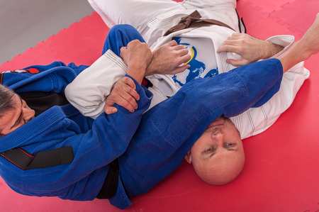 Brazilian jiu jitsu training in traditional kimono. Parterre and ground lock techniques Stock Photo