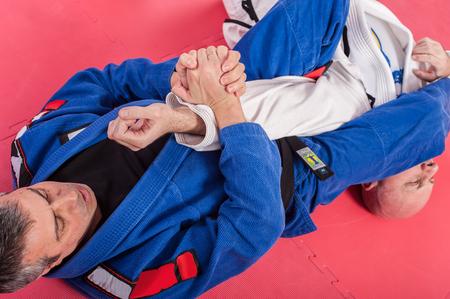 Brazilian jiu jitsu training in traditional kimono. Parterre and ground lock techniques 스톡 콘텐츠