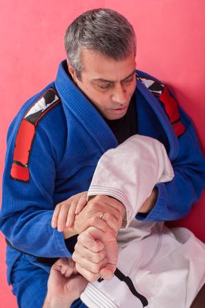 Brazilian jiu jitsu training in traditional kimono. Parterre and ground lock techniques Stock Photo