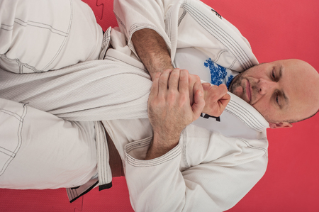 BJJ Brazilian jiu-jitsu training demonstration in traditional kimono. Juji Gatame detail