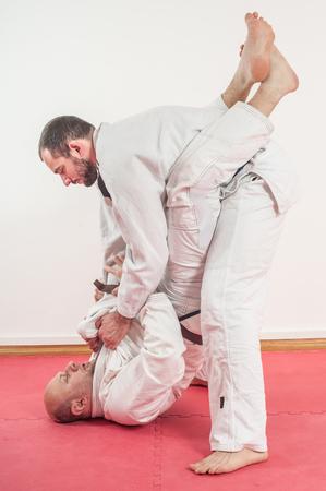 BJJ Brazilian jiu-jitsu training demonstration in traditional kimono. Standing in Closed guard