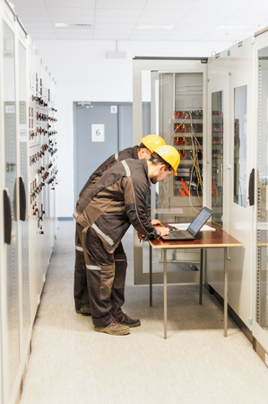 Two maintenance engineers inspect relay protection system with laptop computer. Bay control unit. Medium voltage switchgear
