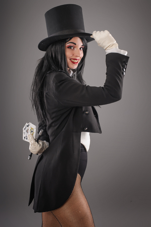 Pretty female magician dressed in performer costume suit with magic wand and playing cards. Studio shoot Banco de Imagens