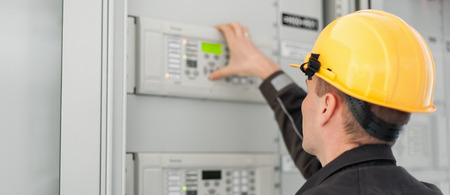 Close up of maintenance engineer testing medium voltage switchgear and bay control unit. Relay protection system