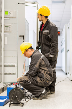 Two field service crew engineers inspect system with relay test set equipment. Relay and protection testing