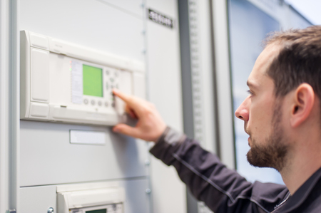 Maintenance engineer testing medium voltage switchgear and bay control unit. Relay protection system Stock Photo