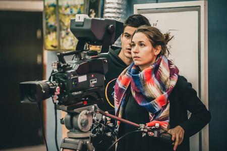 Hinter den Kulissen. Kameramann und Assistent drehen die Filmszene mit der Kamera im Filmstudio