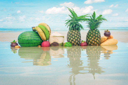Closeup of exotic and colorful tropical fresh fruit on the beach. Summer healthy vitamin mix wallpaper. Water mirror reflection