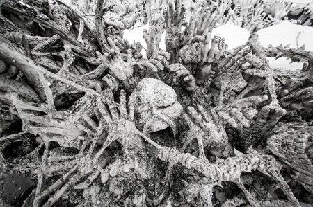 WAT RONG KHUN - WHITE TEMPLE, CHIANG RAI THAILAND - CIRCA MAY 2018. Closeup detail of metamorphic horror screaming face between sculpture of hundreds outreaching hands