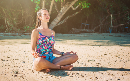 Fit woman relaxing and practicing yoga on the summer  beach. Relax and meditate concept Stock Photo