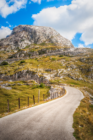 Narrow mountain pass road winds through rocky moorland climbing. Durmitor, Montenegro