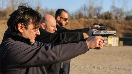 Group of people practice gun shoot on target on outdoor shooting range. Civilian team weapons training