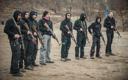 Large team, group of civilian people have action training with rifle machine gun on outdoor shooting range
