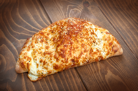 Italian pirogue pizza on wooden table with melting baked cheese. Delicious italian fast food. Calzone pizza Stock Photo