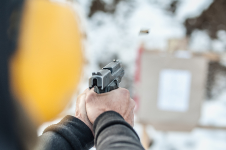 Detail back view of shooter holding gun in hand and shooting on target, close up. Shooting range Stockfoto
