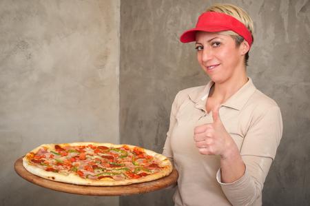 Female chef remove fresh italian pizza from stove. Tasty italian fast food picante pizza Reklamní fotografie