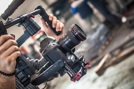 Videographer using stadicam, making video of machine at factory. Close up Reklamní fotografie