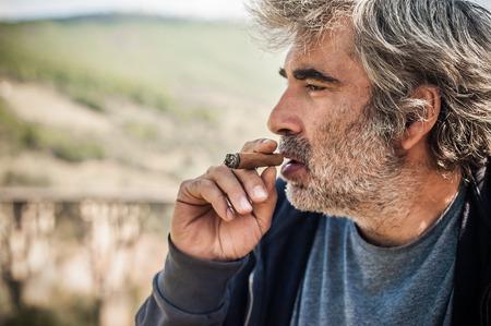 Portrait of bearded caucasian man smoking a cigar. Close up