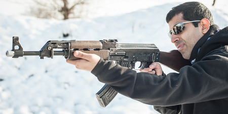 Front view gun point of riffle machine gun. Firearm shooting and weapons training. Winter snow background on outdoor shooting range