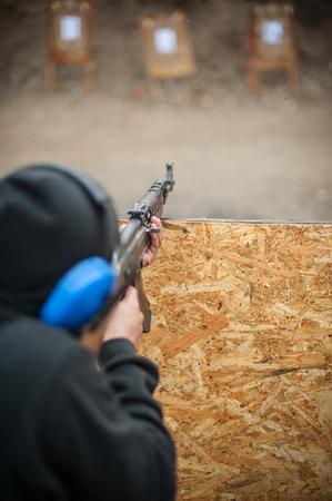 Combatti l'addestramento al tiro con la mitragliatrice da dietro e intorno a una copertura o una barricata. Corsi di tiro tattico di combattimento avanzato su poligono di tiro