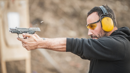 Vue détaillée du tireur tenant un pistolet et de l'entraînement au tir tactique, gros plan. Champ de tir