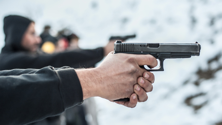 Close-up detail view of shooter practice handgun shooting on target in row group of people on the shooting range