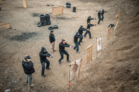 Large group of students with two instructors practice gun shooting on outdoor shooting range. Civilian team weapons training and course