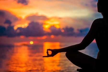 Woman meditating, relaxing in yoga pose at sunset, zen meditation. Silhouette in lotus pose. Mind body spirit concept Stock fotó