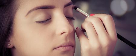 Woman face makeup. Professional makeup artist enhances the eyebrows on the female face Archivio Fotografico