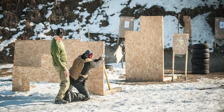 L'instructeur sur le champ de tir enseigne à son élève le tir au pistolet tactique derrière et autour d'une couverture ou d'une barricade. Tir aux armes à feu et entraînement aux armes.