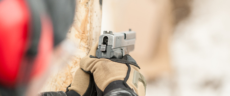 Close-up detail view of hands in gloves holding gun. Shooting range Stock fotó