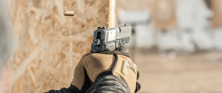 Close-up detail view of hands in gloves holding gun. Shooting range Stock Photo