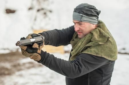 Vista detallada del tirador sosteniendo la pistola en la mano y disparando, de cerca. Rango de disparo Foto de archivo
