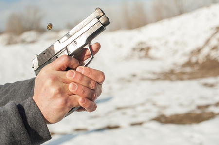 Close-up detail view of shooter hands holding gun and shooting. Shooting range Stock Photo