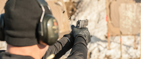 Detail view of shooter holding gun in hand and shooting, close up. Shooting range