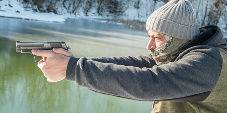 Detail view of shooter holding gun in hand and shooting on the winter lake water background Stock Photo