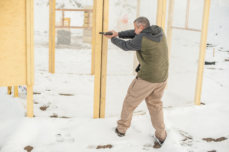 Instructor demonstrate body position of combat gun shooting from behind cover or barricade. Advanced fighting tactical shooting courses on shooting range Reklamní fotografie