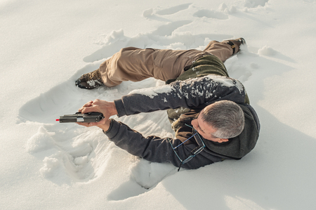 Instructor demonstrate body position of combat gun shooting at winter deep snow. Advanced fighting tactical shooting courses on outdoor shooting range Reklamní fotografie