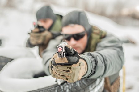 Two military and army special forces soldier direct front view gun point close-up detail of gun with safety stick. Outdoor shooting range on cold and snow winter day
