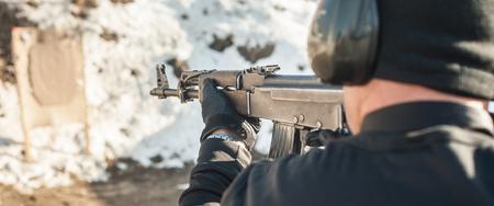 Civilian shooting training from rifle machine gun on outdoor shooting range. Winter and snow season Stock Photo