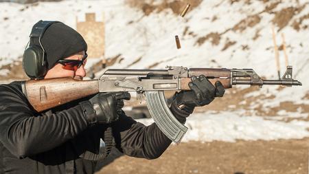 Civilian shooting training from rifle machine gun on outdoor shooting range. Winter and snow season