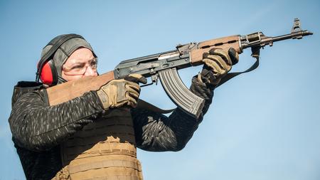 Soldato dell'esercito militare in azione combattimento tattico tiro dalla mitragliatrice fucile. Inverno all'aperto e stagione della neve