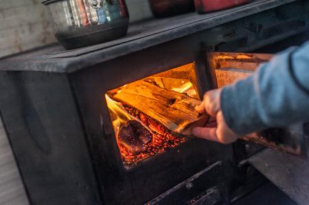 Man putting log to wood burning stove. Close up Stok Fotoğraf - 123223470
