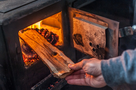 Man putting log to wood burning stove. Close up