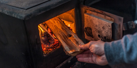 Man putting log to wood burning stove. Close up