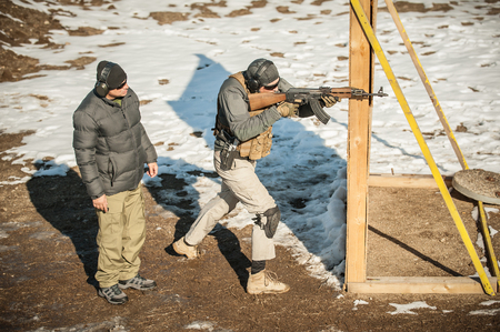 Instructor and his student had rifle machine gun shooting training on outdoor shooting range. Winter and snow cold season Reklamní fotografie